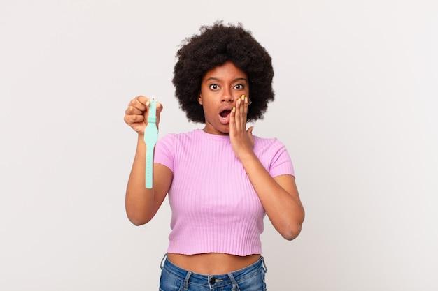 Afro kobieta czuje się zszokowana i przestraszona, wygląda na przerażoną z otwartymi ustami i rękami na policzkach