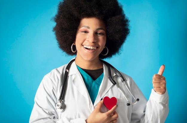 Afro kobieta kardiolog w mundurze i stococope uśmiecha się patrząc w kamerę, trzymając serce i wykonując pozytywny gest