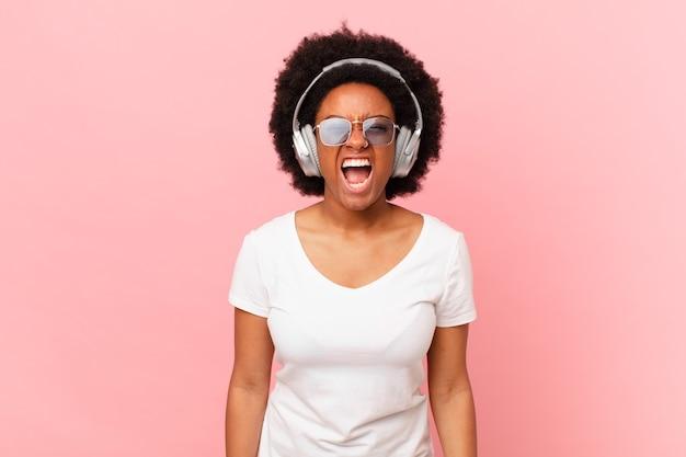 """Afro kobieta krzycząca agresywnie, wyglądająca na bardzo rozgniewaną, sfrustrowaną, oburzoną lub zirytowaną, krzyczącą """"nie"""". koncepcja muzyki"""