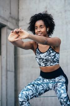 Afro kobieta lekkoatletycznego ćwiczenia i robi przysiadową nogę na świeżym powietrzu. pojęcie sportu i zdrowego stylu życia.