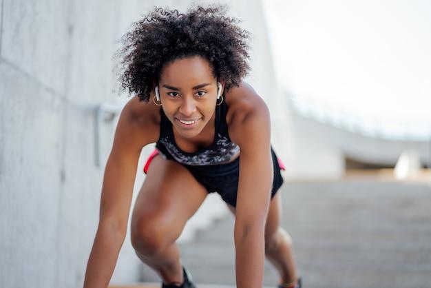 Afro kobieta lekkoatletycznego gotowa do biegania na zewnątrz. sport i zdrowy tryb życia.