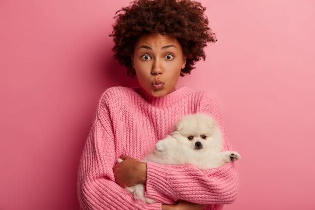 Afro kobieta ma złożone usta, nosi małego szpica pomorskiego do salonu fryzjerskiego, dba o zwierzę, nosi różowy sweter