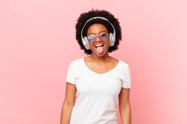 Afro kobieta o pogodnym, beztroskim, buntowniczym nastawieniu, żartująca i wysuwająca język, dobrze się bawiąca. koncepcja muzyki