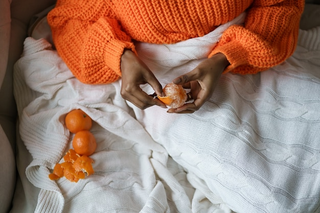 Afro kobieta ręce obiera dojrzałe słodkie mandarynki, nosić pomarańczowy sweter, leżąc w łóżku pod kratą