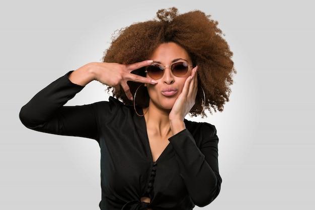 Afro kobieta robi chłodnemu gestowi, twarzy zbliżenia twarzy zbliżenie