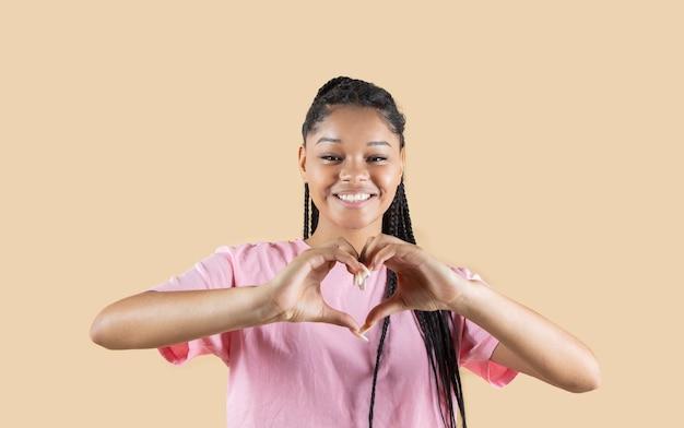 Afro kobieta robi gest serca z miejsca na kopię