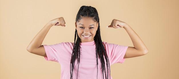 Afro kobieta robi gest siły i zwycięstwa na żółtym tle