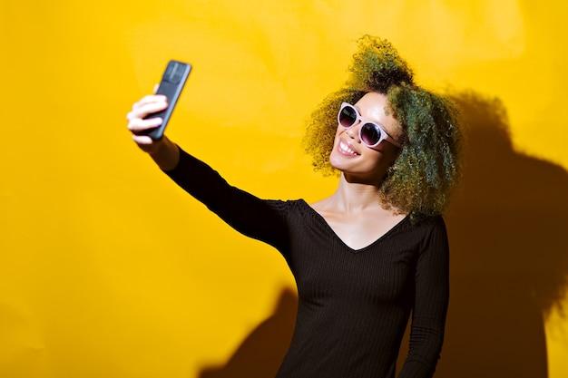 Afro kobieta robi selfie w okularach przeciwsłonecznych na żółtym tle