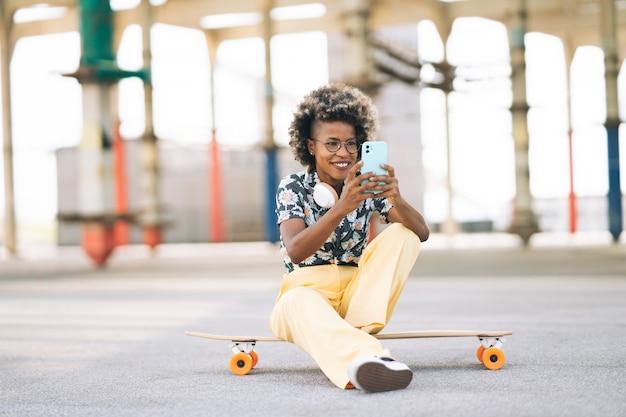 Afro kobieta siedzi na deskorolce, używając swojego telefonu, szczęśliwa na ulicy