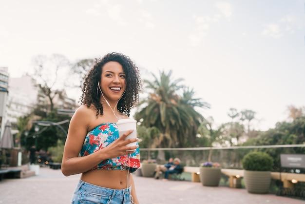 Afro kobieta słucha muzyka podczas gdy trzymający filiżankę kawy.