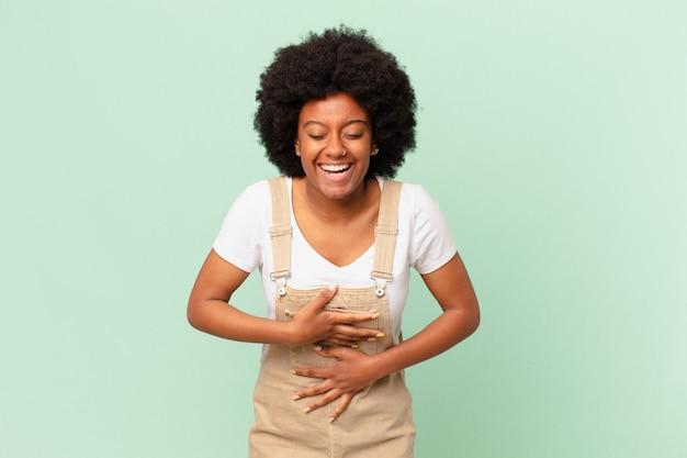 Afro kobieta śmiejąca się głośno z jakiegoś zabawnego żartu, czująca się szczęśliwa i wesoła, mająca zabawną koncepcję szefa kuchni