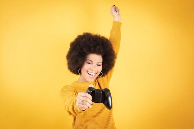Afro kobieta szczęśliwa trzymająca kontroler gier wideo na żółtym tle