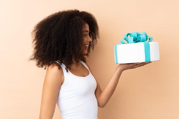 Afro kobieta trzyma biały tort z niebieską kokardą