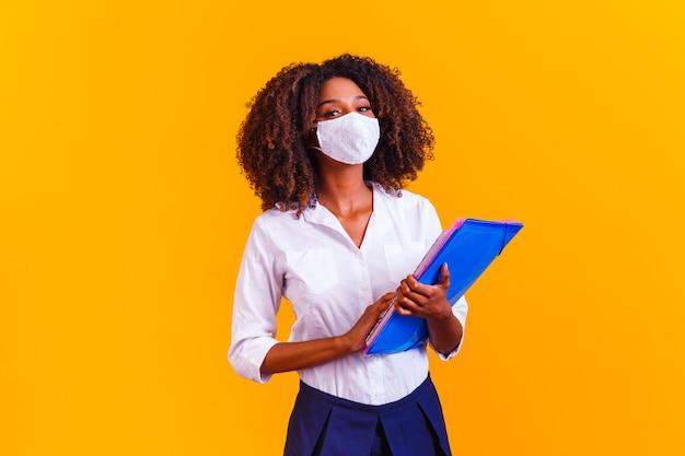 Afro kobieta trzyma książki na sobie maskę ochronną. wróć na zajęcia przez kwarantannę