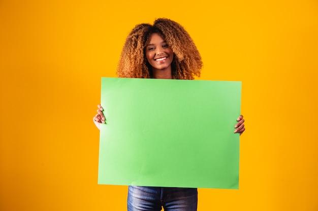 Afro kobieta trzyma plakat z zielonym chromem.