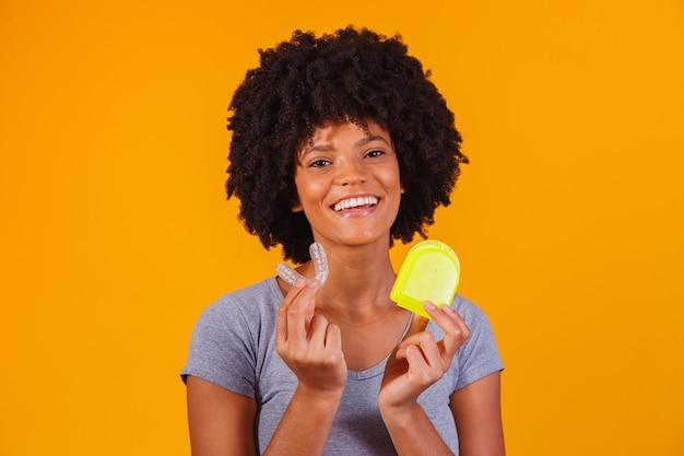 Afro kobieta trzymając talerz do wybielania. niewidzialne urządzenie.