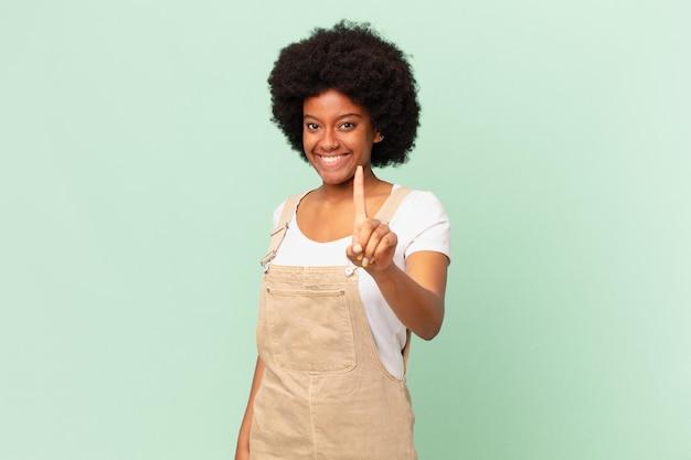 Afro kobieta uśmiecha się dumnie i pewnie robiąc triumfalną pozę numer jeden, czując się jak lider koncepcji szefa kuchni