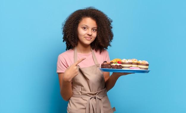 Afro kobieta uśmiecha się radośnie, czuje się szczęśliwa i wskazuje na bok i do góry, pokazując obiekt w przestrzeni kopii. humorystyczny koncepcja piekarza