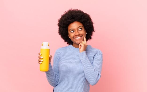Afro kobieta uśmiecha się radośnie i marzy lub wątpi, patrząc w bok. koncepcja smoothie