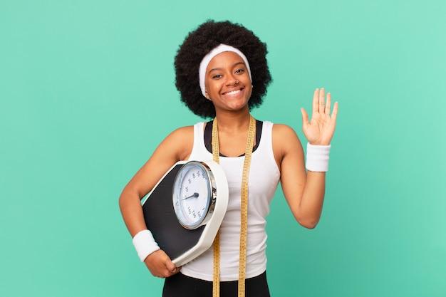 Afro kobieta uśmiecha się radośnie i radośnie, machając ręką, witając cię i pozdrawiając lub żegnając się z koncepcją diety