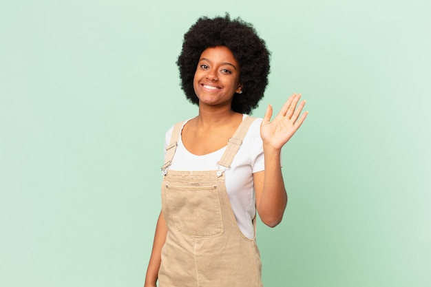 Afro kobieta uśmiecha się radośnie i radośnie, machając ręką, witając cię i pozdrawiając lub żegnając się z koncepcją szefa kuchni