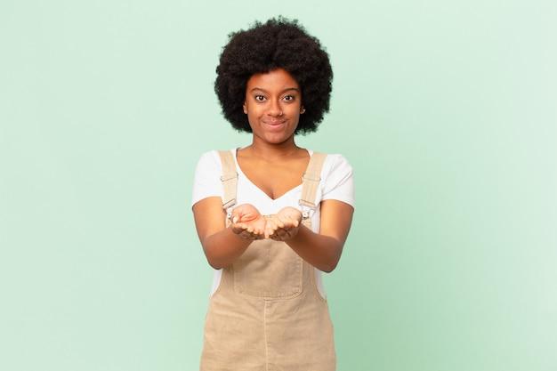 Afro kobieta uśmiechająca się radośnie z przyjaznym, pewnym siebie, pozytywnym spojrzeniem, oferująca i pokazująca koncepcję obiektu lub koncepcji szefa kuchni