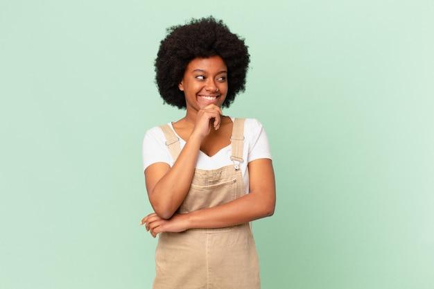 Afro kobieta uśmiechająca się ze szczęśliwym, pewnym siebie wyrazem twarzy z ręką na brodzie, zastanawiająca się i patrząca w stronę koncepcji szefa kuchni