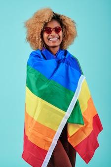 Afro kobieta uśmiechnięta, owinięta tęczową flagą, aby wspierać społeczność lgbtq na odosobnionym tle.
