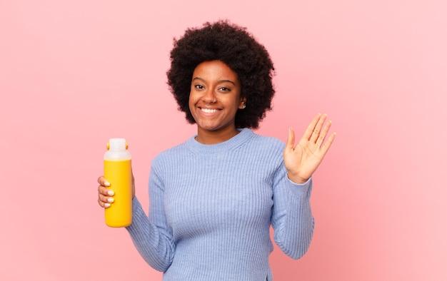 Afro kobieta uśmiechnięta radośnie i radośnie, machająca ręką, witająca i pozdrawiająca cię lub żegnająca. koncepcja smoothie