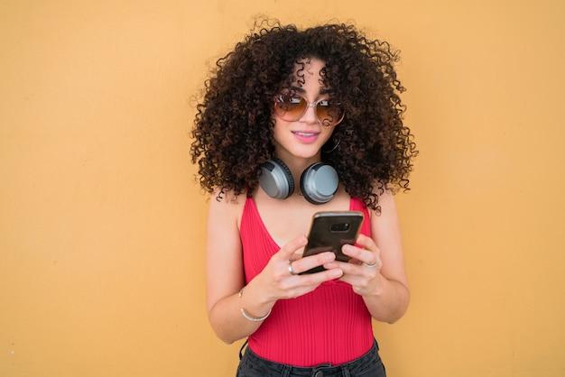 Afro kobieta używa jej telefon komórkowego.