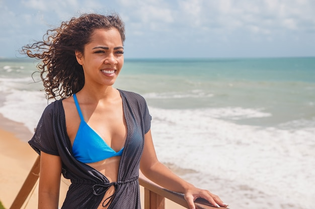 Afro kobieta w bikini na wakacje na plaży.