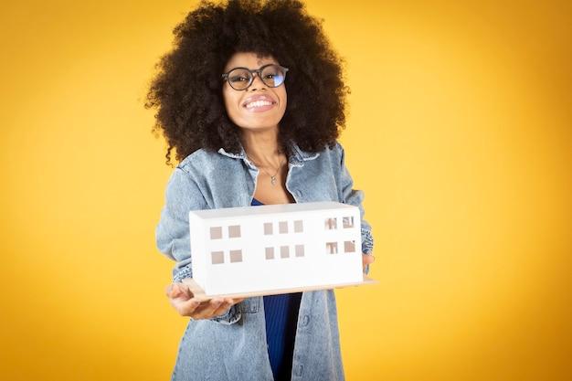 Afro kobieta w okularach architekt, żółte tło