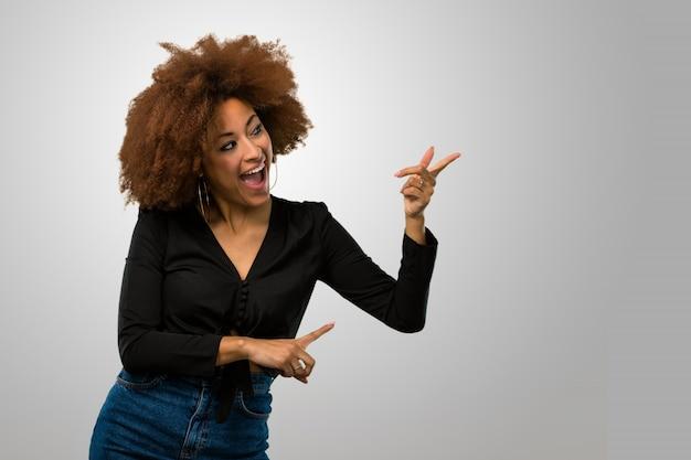 Afro kobieta wskazuje na bok