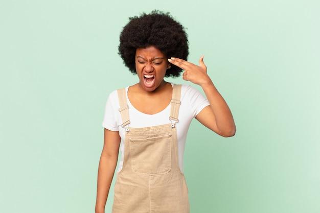 Afro kobieta wyglądająca na niezadowoloną i zestresowaną, samobójczy gest, robiący znak pistoletu ręką, wskazujący na koncepcję szefa kuchni