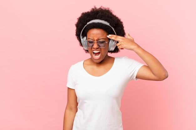 Afro kobieta wyglądająca na niezadowoloną i zestresowaną, samobójczy gest, wykonując ręką znak pistoletu, wskazując na głowę. koncepcja muzyki