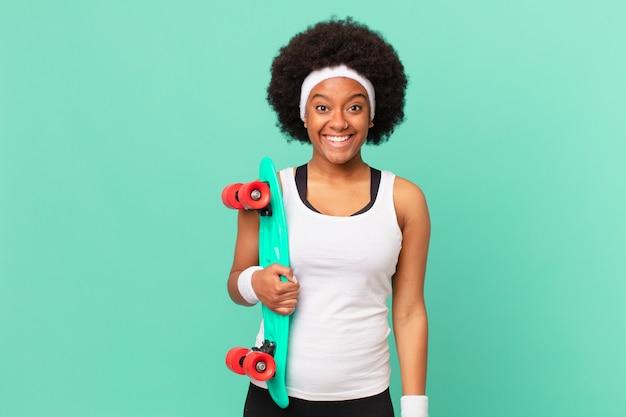 Afro kobieta wyglądająca na szczęśliwą i mile zaskoczoną, podekscytowaną o zafascynowanym i zszokowanym wyrazie twarzy. koncepcja deskorolki