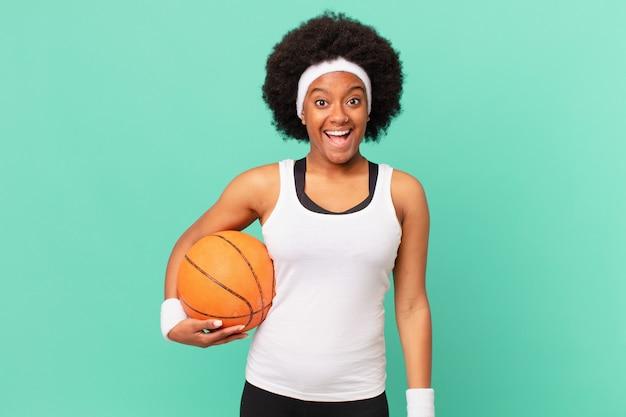 Afro kobieta wyglądająca na szczęśliwą i mile zaskoczoną, podekscytowaną o zafascynowanym i zszokowanym wyrazie twarzy. koncepcja koszykówki