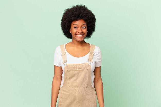 Afro kobieta wyglądająca na szczęśliwą i mile zaskoczoną, podekscytowaną zafascynowaną i zszokowaną koncepcją szefa kuchni