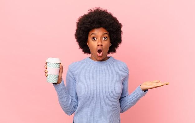 Afro kobieta wyglądająca na zaskoczoną i zszokowaną, z opuszczoną szczęką trzymająca przedmiot z otwartą dłonią z boku. koncepcja kawy