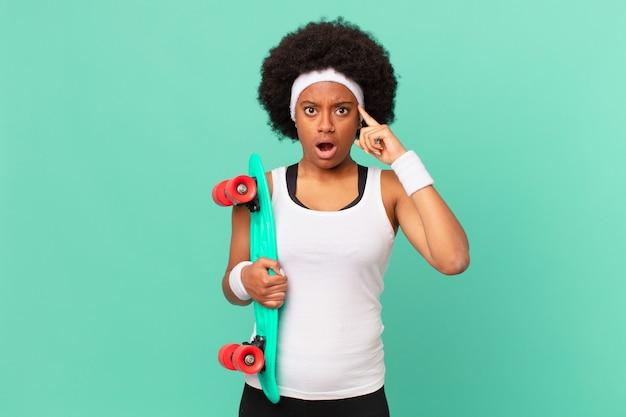 Afro kobieta wyglądająca na zaskoczoną, z otwartymi ustami, zszokowaną, realizującą nową myśl, pomysł lub koncepcję. koncepcja deskorolki