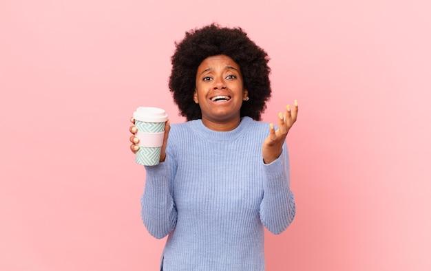 Afro kobieta wyglądająca na zdesperowaną i sfrustrowaną, zestresowaną, nieszczęśliwą i zirytowaną, krzyczącą i krzyczącą. koncepcja kawy