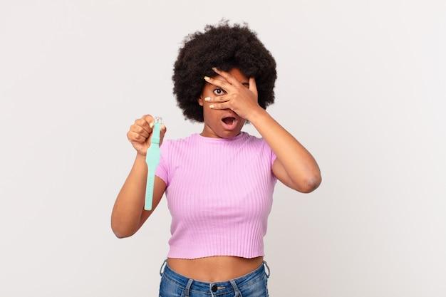 Afro kobieta wyglądająca na zszokowaną, przestraszoną lub przerażoną, zakrywającą twarz dłonią i zerkającą między palcami koncepcja zegarka