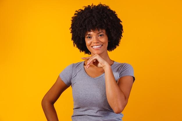 Afro kobieta z czarnymi włosami mocy uśmiecha się patrząc na kamerę