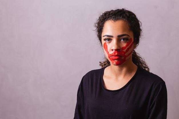 Afro kobieta z odciskiem dłoni na ustach na rzecz świadomości kobiecości. przemoc domowa
