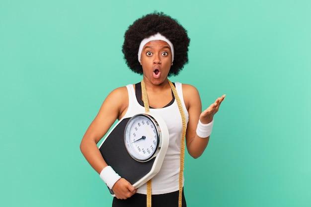 Afro kobieta z otwartymi ustami i zdumiona, zszokowana i zdumiona niewiarygodną koncepcją diety niespodzianki