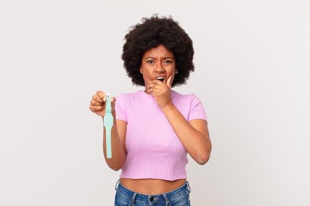Afro kobieta z szeroko otwartymi ustami i oczami i ręką na brodzie, czując się nieprzyjemnie zszokowana, mówiąc co lub wow watch concept