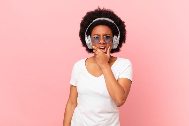 Afro kobieta z szeroko otwartymi ustami i oczami iz ręką na brodzie, czując się nieprzyjemnie zszokowana, mówiąca co lub wow. koncepcja muzyki