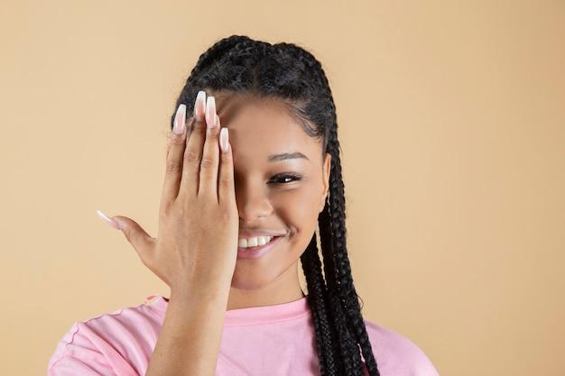Afro kobieta zakrywa pół twarzy jedną ręką, jednocześnie się uśmiechając