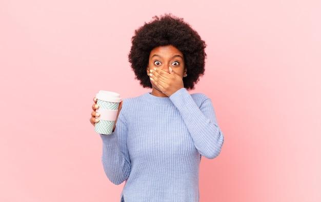 """Afro kobieta zakrywająca usta dłońmi ze zszokowanym, zdziwionym wyrazem twarzy, zachowująca tajemnicę lub mówiąca """"ups"""". koncepcja kawy"""