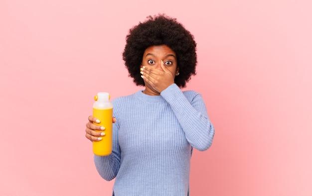 """Afro kobieta zakrywająca usta dłońmi ze zszokowanym, zdziwionym wyrazem twarzy, zachowująca tajemnicę lub mówiąca """"ups"""". koncepcja smoothie"""